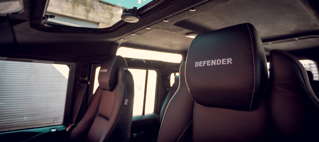 Inside view of Defender with black leather and embroidered headrests.