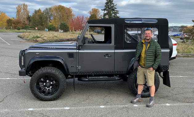 Man standing next to a Defender 90