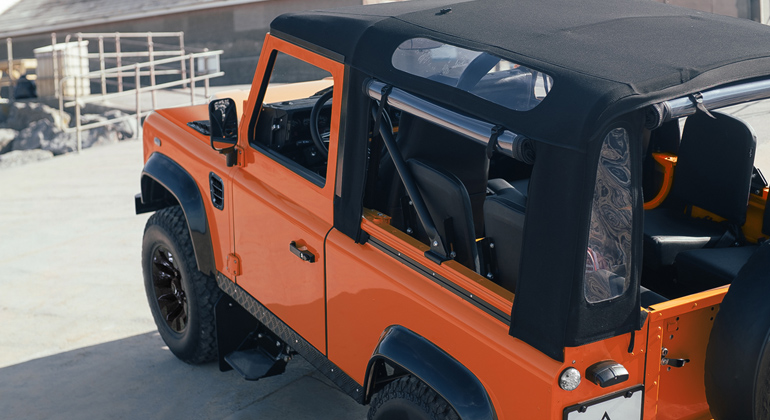 Side view of orange Defender 90 soft-top on the beach