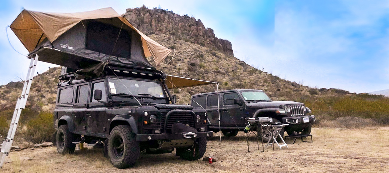 A Land Rover Defender with roof-top tent and Jeep Wrangler