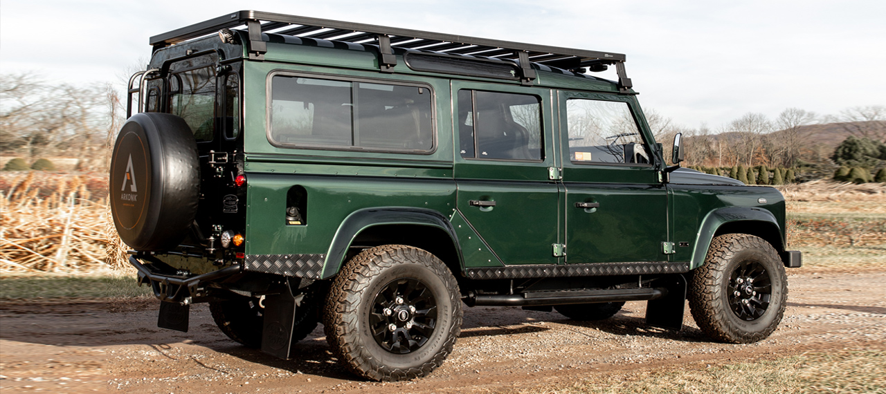 Side view of green Land Rover Defender on dirt track