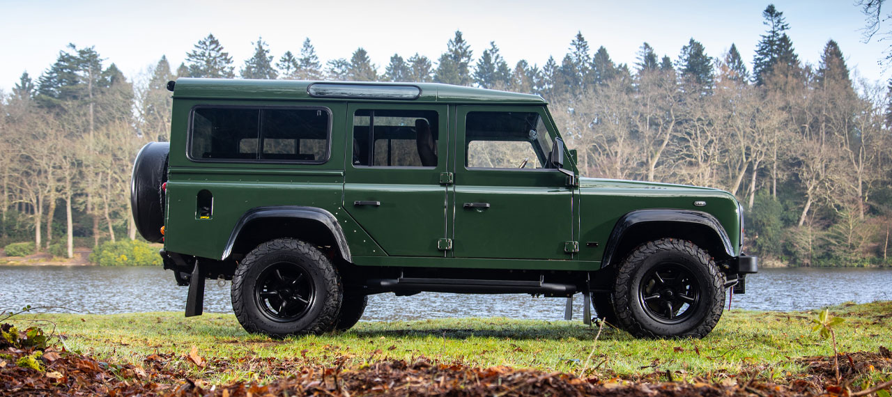Side view of Coniston Green Defender 110 with view of lake behind