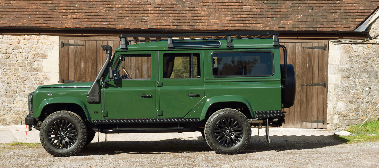 Side view of Coniston Green Defender with wading kit in front of barn