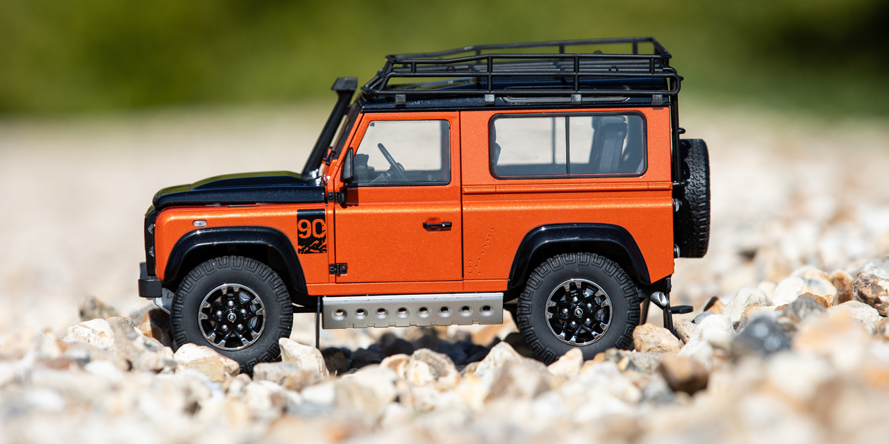 Side view of a small orange and black model of a Defender