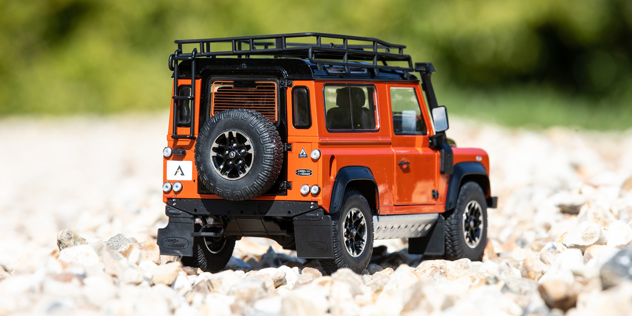 Rear view of a small orange and black model Defender
