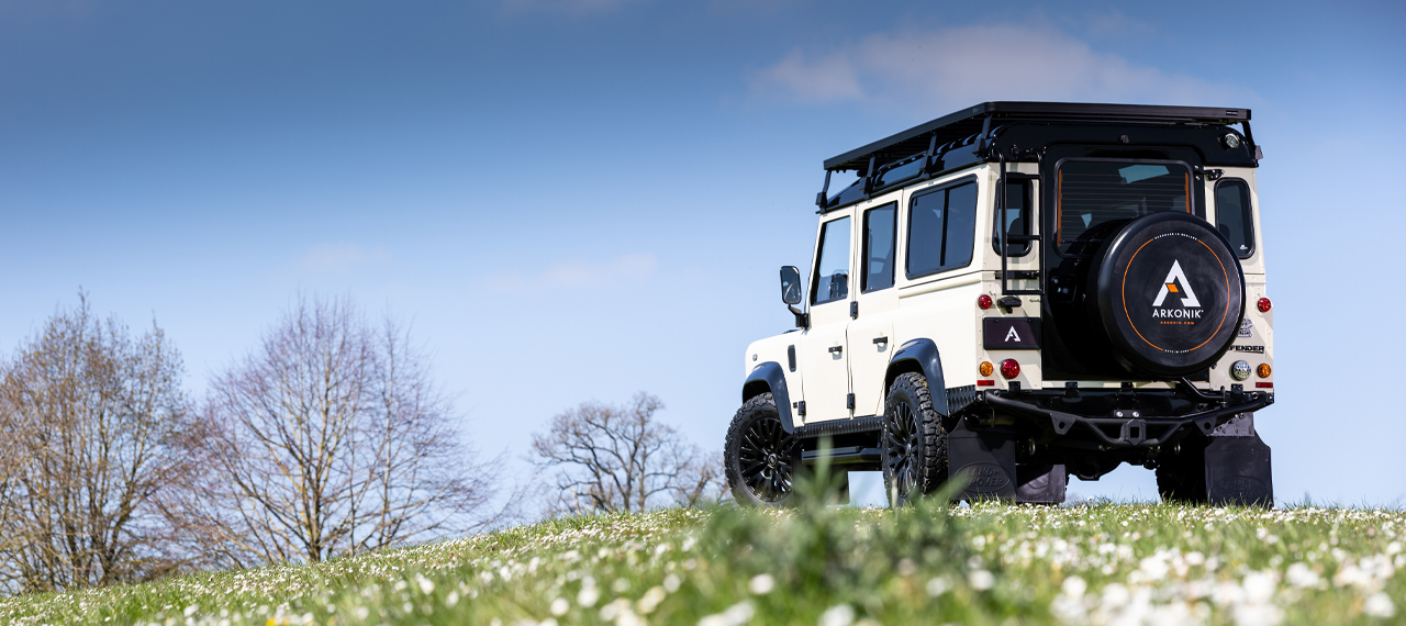 Rear view of a Limestone Beige and Black Arkonik Defender in field with blue sky