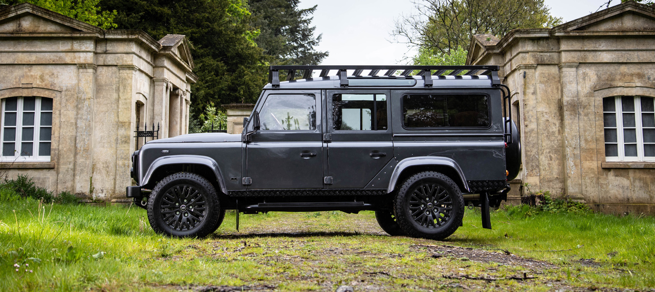 Side view of Bonatti Grey Defender 110 in front of ruins
