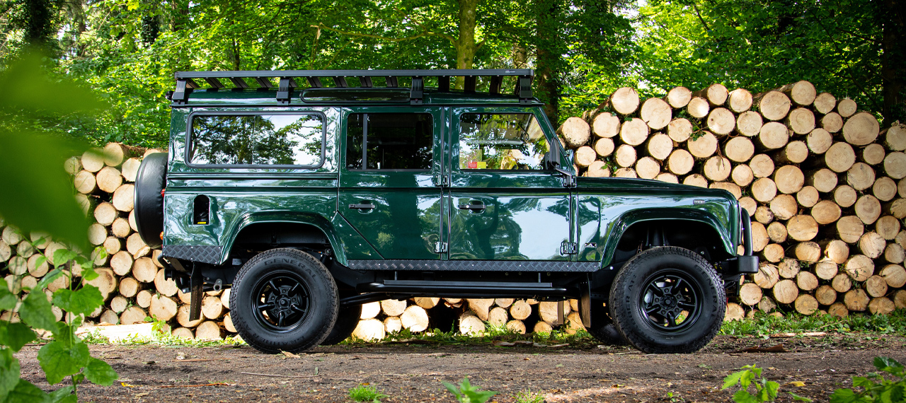 Side view of Epsom Green Arkonik Defender 110 in front of logpile